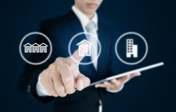 Businessman pressing real estate icons on screen. Business investment in real estate, town house, single home and condominium. Businessman pressing real estate royalty free stock images