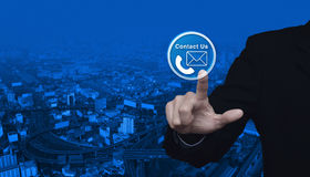 Businessman pressing telephone and mail icon button over city to Royalty Free Stock Image