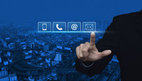 Businessman pressing telephone, mobile phone, at and email butto. Ns over city tower and street blue tone background, Customer support concept Royalty Free Stock Images