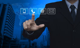 Businessman pressing telephone, mobile phone, at and email butto. Ns over map and city tower, Customer support concept, Elements of this image furnished by NASA Royalty Free Stock Photography