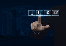 Businessman pressing telephone, mobile phone, at and email butto. Ns over map and city tower, Customer support concept, Elements of this image furnished by NASA Royalty Free Stock Image