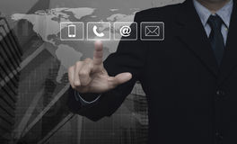 Businessman pressing telephone, mobile phone, at and email butto. Ns over map and city tower, Customer support concept, Elements of this image furnished by NASA Stock Image