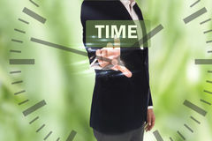 Businessman pressing time button on virtual screens and clock Stock Image