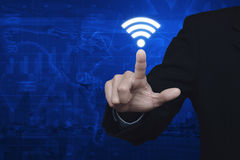 Businessman pressing wi-fi icon over map and city background, Te Stock Photography