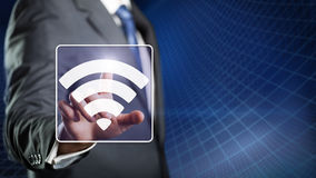 Businessman pressing a wifi symbol Royalty Free Stock Images