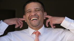 Businessman pretends not to listen with his fingers in his ears stock video footage