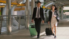Business people walking and drag the baggage along open passage. The businessman and pretty businesswoman walking and dragging a baggage with wheel along the Royalty Free Stock Photography