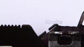 Businessman prints word marketing on retro typewriter. Close up. Businessman prints word marketing on a retro typewriter, a new generation in the financial stock footage