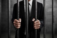 Businessman in prison hold bars. Businessman in prison holding bars stock image