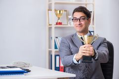 The businessman with prize cup for achievements in office. Businessman with prize cup for achievements in office stock images