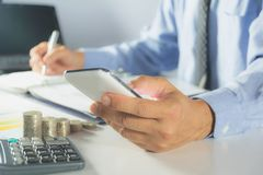 Businessman process with writing and using smart phone. Businessman working the project on table Stock Photo