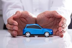 Businessman Protecting Blue Car. Businessman`s Hand Protecting Small Miniature Blue Car royalty free stock images