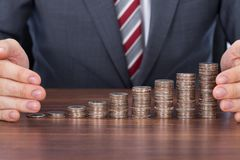 Businessman Protecting Coin Stacks At Desk Royalty Free Stock Image