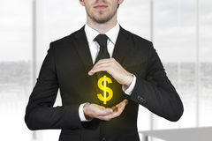 Businessman protecting dollar symbol Stock Images