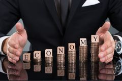 Businessman protecting economy blocks on stacked coins Royalty Free Stock Photography