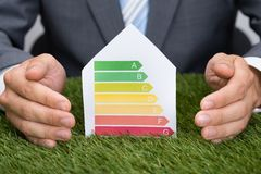Businessman Protecting Energy Consumption Label On Grass Stock Photo