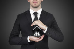 Businessman protecting family home Stock Images