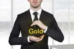 Businessman protecting gold with hands Stock Photos