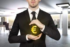 Businessman protecting golden eurosymbol. Businessman in modern office protecting golden euro symbol Stock Image