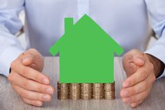 Businessman protecting green model house on stacked coins Stock Photography