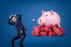 Businessman protecting himself with hands and pink piggy bank over red dynamite sticks with lit fuse on blue background stock photography