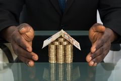 Businessman Protecting House Made Of Money. Close-up Of Businessman Hands Protecting House Made Of Money royalty free stock photography