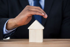 Businessman protecting house model with hands Stock Images