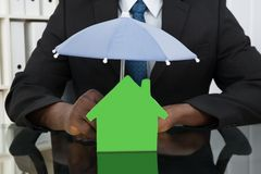 Businessman Protecting House Model With Umbrella Royalty Free Stock Photo