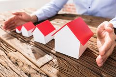 Businessman Protecting The House Models With Hands Royalty Free Stock Images
