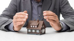 Home insurance plans. Businessman protecting a model house with his hands: home insurance, investments and real estate concept stock photos