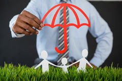 Businessman protecting paper cut out family with umbrella Stock Image