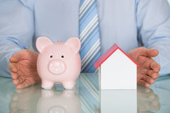 Businessman Protecting Piggy Bank And House Model Royalty Free Stock Photography