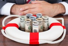 Businessman protecting rolled bank notes with lifebuoy Stock Images