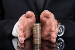 Businessman protecting stacked coins Royalty Free Stock Photo
