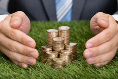 Businessman protecting stacked coins on grass Stock Images
