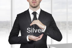 Businessman protecting word silver with hands Royalty Free Stock Image