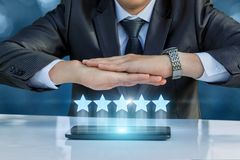 Businessman protects a rating out of five stars. Business man protects a rating out of five stars royalty free stock photography
