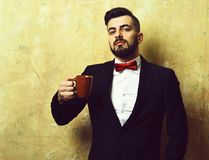 Businessman with proud and happy face holds brown cup. Of coffee, wears classic black suit and red bow. Old cracked light yellow wall background, concept of Royalty Free Stock Photo
