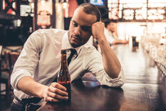 Businessman in pub. Handsome sad Afro American businessman is drinking beer and leaning on the bar counter while sitting at the pub Stock Photo