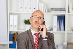 Businessman Puckering Lips While Using Cordless Phone Stock Photography