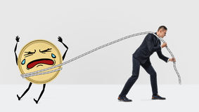 A businessman pulling away an unwilling and crying large golden coin with a rope. Keep budget under control. Savings and loans. Wise spending Royalty Free Stock Photography