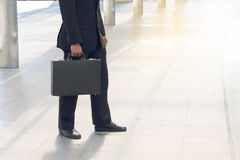Businessman pulling a bag in a big city. Royalty Free Stock Photos