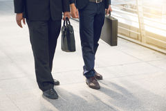 Businessman pulling a bag in a big city. Stock Photo