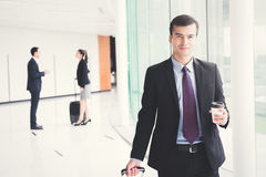Businessman pulling baggage and holing coffee cup while walking Royalty Free Stock Photos