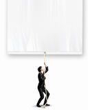 Businessman pulling banner. Image of businessman pulling blank banner. Place for text Stock Photos