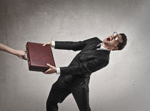 Businessman pulling a briefcase Royalty Free Stock Photography