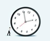 Businessman pulling clock Stock Image
