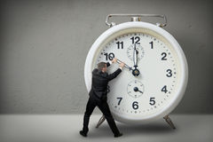 Businessman pulling a clock hand royalty free stock image