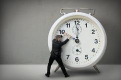 Businessman pulling a clock hand