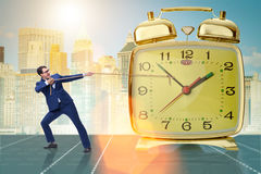The businessman pulling clock in time management concept. Businessman pulling clock in time management concept Stock Photography